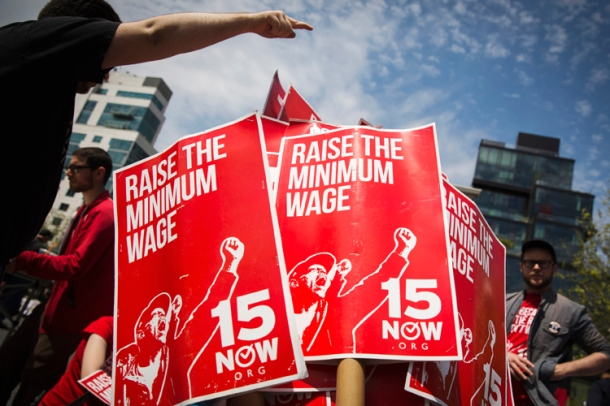 Demonstrators prepare signs supporting the raising of the federal minimum wage during May Day demonstrations in New York